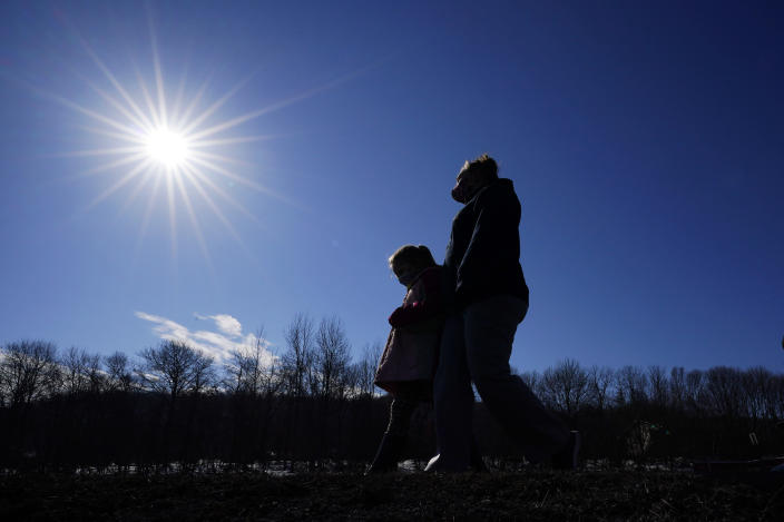 Kacie Thompson, left, 9, walks with her mother, Melissa Weirich, after visiting the former home of Kacie's friend, Ava Lerario, Thursday, March 11, 2021, in Lansford, Pa. On May 26, 2020, 9-year-old Ava; her mother, Ashley Belson, and Ava's father, Marc Lerario, were found fatally shot. (AP Photo/Matt Slocum)