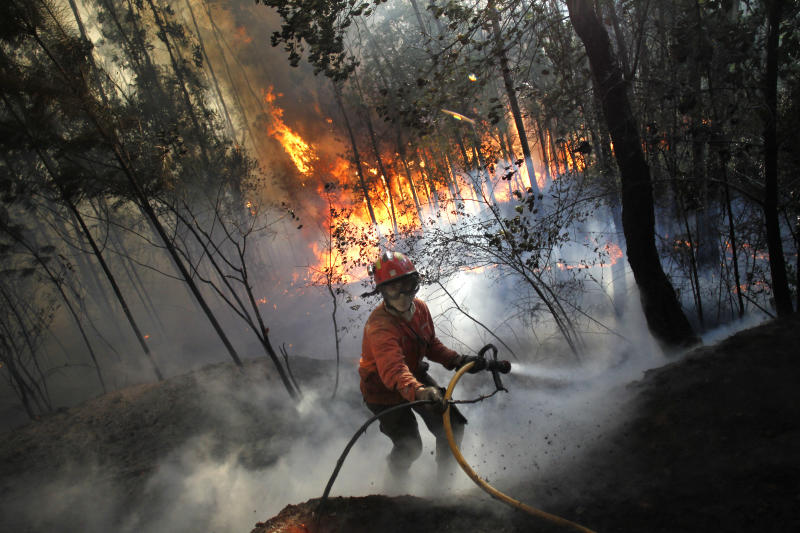 A firefighter steps back while working to douse a fire in Alvaiazere, center Portugal, Tuesday, Sept. 4, 2012. A Portuguese official says authorities have asked other European countries to send help as the country's firefighters struggle to contain forest blazes being fueled by high temperatures and strong winds. More than 1,700 firefighters, almost 500 vehicles and 13 aircraft fought blazes mostly in the north of the country. (AP Photo/Francisco Seco)