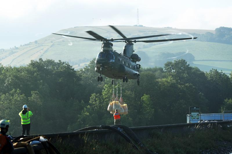 An RAF Chinook helicopter flies in sandbags to help repair the dam at Toddbrook reservoir near the village of Whaley Bridge in Derbyshire after it was damaged by heavy rainfall. PRESS ASSOCIATION Photo. Picture date: Friday August 2, 2019. See PA story WEATHER Rain. Photo credit should read: Yui Mok/PA Wire
