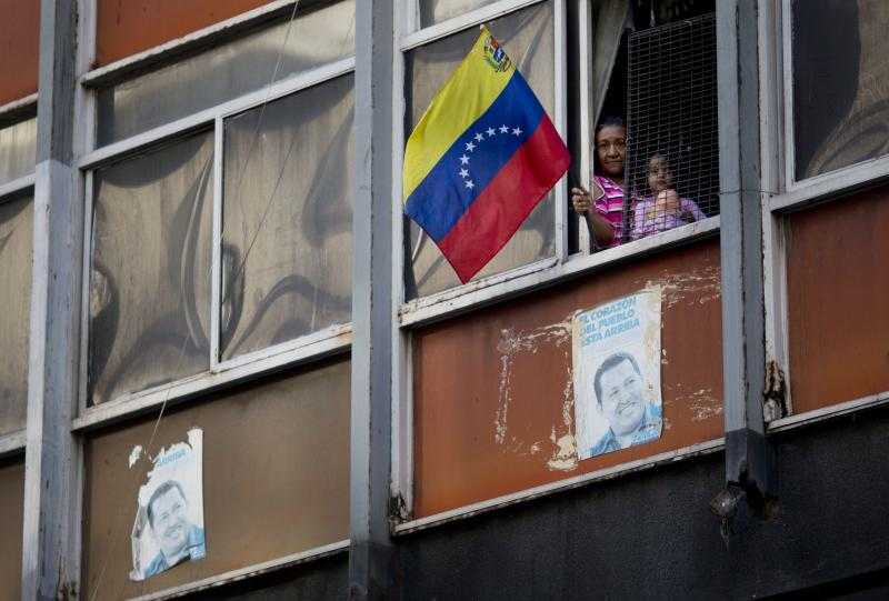 In this Feb. 25, 2014 photo, a woman waves a Venezuelan flag next to a girl inside a poor apartment in downtown in Caracas, Venezuela. There is plenty of discontent among the lower classes but the students have failed to capitalize on it. The students have not clearly articulated an agenda, says Luis Vicente Leon, director of the Datanalisis polling firm, and are divided among moderates and radicals just like the main opposition parties. (AP Photo/Rodrigo Abd)