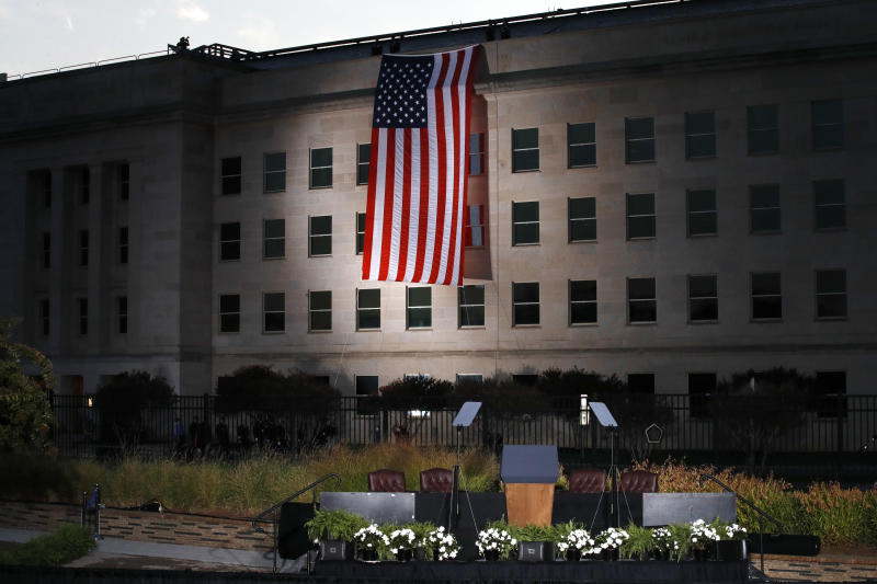 The podium awaits the arrival of President Donald Trump as a U.S. flag is unfurled at the Pentagon on the 16th anniversary of the September 11th attacks Monday, Sept. 11, 2017. (AP Photo/Jacquelyn Martin)