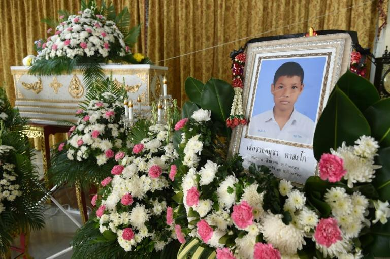A portrait of 13-year-old Muay Thai boxer Anucha Tasako is displayed next to his coffin during a funeral at a Buddhist temple in Samut Prakan province on November 14, 2018. Thais have reacted with shock and anger after Tasako died during a charity bout, reviving calls for a ban on fights between children in the brutal Muay Thai martial art