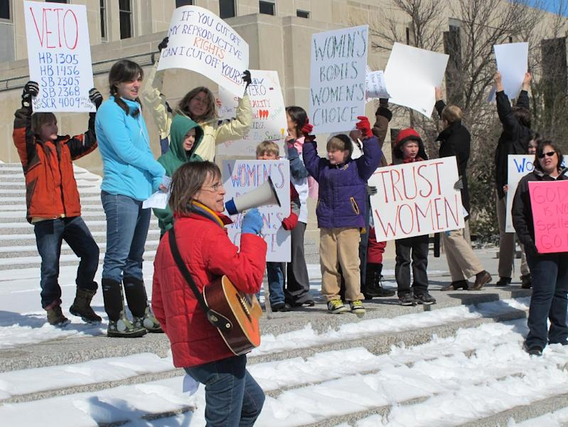FILE - In this March 25, 2013 file photo, Kris Kitko leads chants of protest at an abortion-rights rally at the state Capitol in Bismarck, N.D. Rival legal teams, each well-financed and highly motivated, are girding for high-stakes court battles over the coming months on laws enacted in Arkansas and North Dakota that would impose the nation's toughest bans on abortion. The Arkansas law, approved March 6 when legislators overrode a veto by Democratic Gov. Mike Beebe, would ban most abortions from the 12th week of pregnancy onward. On March 26, North Dakota went even further, with Republican Gov. Jack Dalrymple signing a measure that would ban abortions as early as six weeks into a pregnancy, when a fetal heartbeat can first be detected. (AP Photo/James MacPherson, File)
