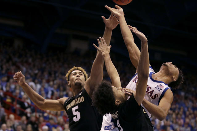 Kansas' Devon Dotson, back, shoots under pressure from Colorado's D'Shawn Schwartz (5) and Daylen Kountz during the first half of an NCAA college basketball game Saturday, Dec. 7, 2019, in Lawrence, Kan. (AP Photo/Charlie Riedel)