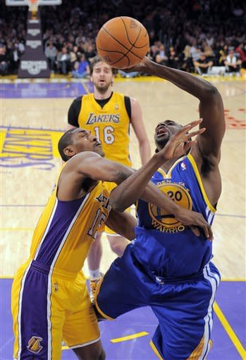 Golden State Warriors power forward Ekpe Udoh, right, is fouled by Los Angeles Lakers small forward Metta World Peace, left, as power forward Pau Gasol, of Spain, looks on during the first half of their NBA basketball game, Friday, Jan. 6, 2012, in Los Angeles. (AP Photo/Mark J. Terrill)