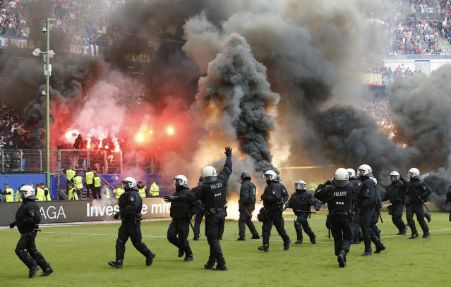 Police officers stand on the pitch when Hamburg fans light fireworks when their team relegates during the German Bundesliga soccer match between Hamburger SV and VfL Borussia Moenchengladbach in Hamburg, Germany, Saturday, May 12, 2018. (AP Photo/Michael Sohn)