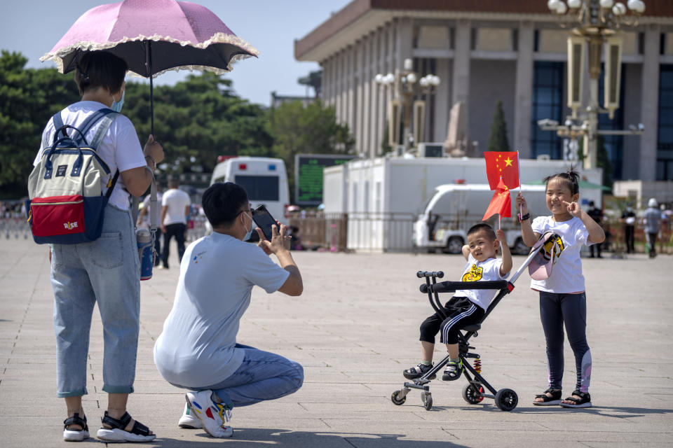 Children hold Chinese flags as they pose for a photo at Tiananmen Square in Beijing, on June 22, 2021. China will now allow couples to have a third child as the country seeks to hold-off a demographic crisis that threatens its hopes of increased prosperity and global influence. (AP Photo/Mark Schiefelbein)