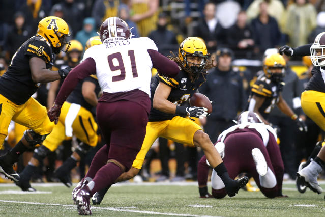 Appalachian State wide receiver Corey Xavier Sutton (2)runs the ball while getting pressure from Texas State defensive lineman Jordan Revels (91) during the first half of an NCAA college football game Saturday, Nov. 23, 2019, in Boone, N.C. (AP Photo/Brian Blanco)