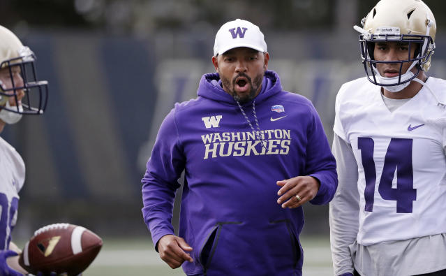 Washington co-defensive coordinator Jimmy Lake works with players at the first practice of spring football for the NCAA college team Wednesday, March 28, 2018, in Seattle. (AP Photo/Elaine Thompson)