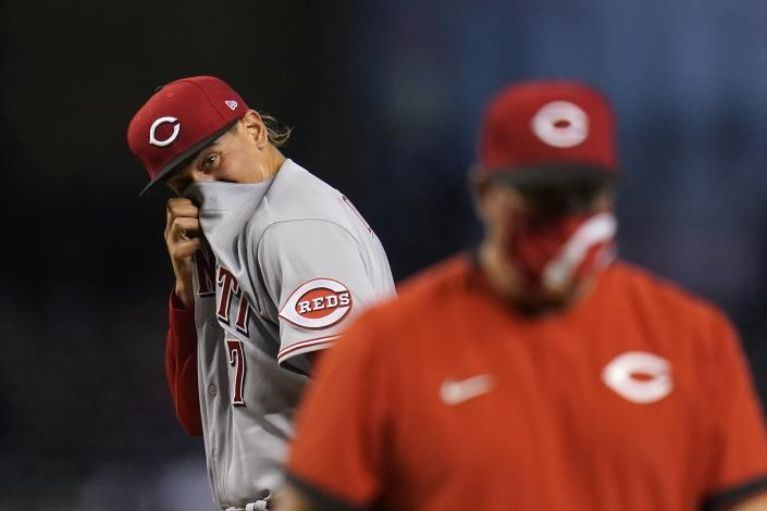 Cincinnati Reds starting pitcher Jose De Leon, left, wipes sweat from his face after getting a visit from Reds pitching coach Derek Johnson, right, as a result of giving up a three-run home run to Arizona Diamondbacks' David Peralta and during the third inning of a baseball game Sunday, April 11, 2021, in Phoenix. (AP Photo/Ross D. Franklin)