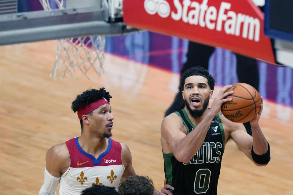 Boston Celtics forward Jayson Tatum (0) drives to the basket past New Orleans Pelicans guard Josh Hart to score the tying points in the second half of an NBA basketball game in New Orleans, Sunday, Feb. 21, 2021. (AP Photo/Gerald Herbert)