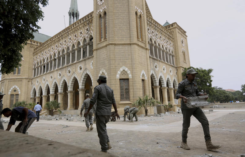 """Workers for Karachi Municipal Corporation remove an artwork of concrete tombstones marking the number of """"extrajudicial killings"""", at Frere Hall in Karachi, Pakistan, Tuesday, Oct. 29, 2019. A Pakistani artist says authorities closed her exhibition in Karachi that sought to denounce police raids led by an infamous officer that had killed hundreds of people. (AP Photo/Fareed Khan)"""