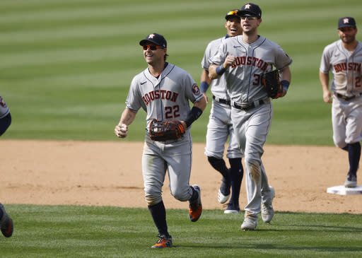 Houston Astros right fielder Josh Reddick, front, smiles as he leads left fielder Kyle Tucker, shortstop Carlos Correa and second baseman Jose Altuve off the field after the ninth inning of a baseball game against the Colorado Rockies Thursday, Aug. 20, 2020, in Denver. Reddick made a diving catch of a line drive off the bat of Colorado Rockies' Trevor Story to notch the final out. (AP Photo/David Zalubowski)
