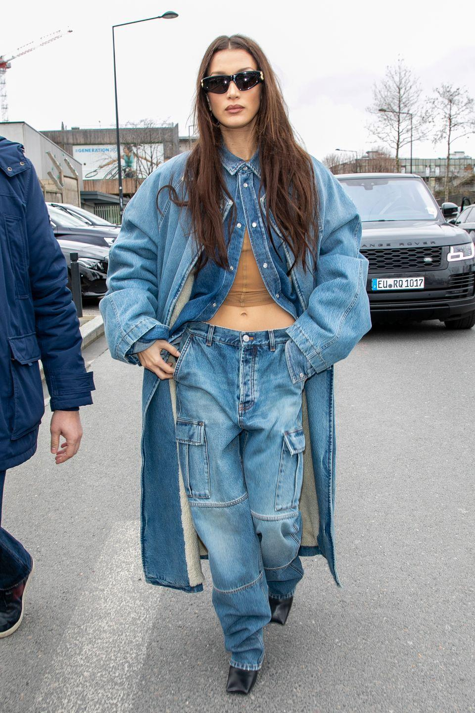 <p>The model wore a double denim ensemble in Paris on March 1. The Californian beauty styled her oversized denim overall coat with a pair of baggy jeans, black square-toe boots and a camel-coloured crop top. </p>
