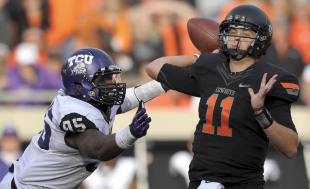 FILE - In this Oct. 27, 2012, file photo, TCU defensive end Devonte Fields, left, pressures Oklahoma State quarterback Wes Lunt, right, during an NCAA college football game in Stillwater, Okla. Field as selected as the AP's Big 12 defensive player of the year, Wednesday, Dec. 5, 2012. (AP Photo/Brody Schmidt, File)