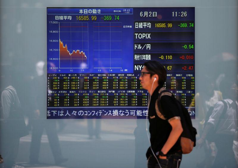 FILE PHOTO: A man walks in front of a screen showing today's movements of Nikkei share average outside a brokerage in Tokyo, Japan, June 2, 2016. REUTERS/Issei Kato