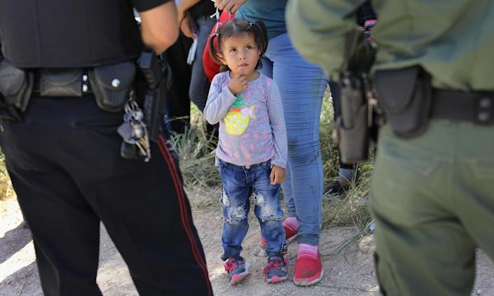 """<span class=""""element-image__caption"""">A Mission police department officer and a US border patrol with a group of Central American asylum seekers before taking them into custody on 12 June near McAllen, Texas.</span> <span class=""""element-image__credit"""">Photograph: John Moore/Getty Images</span>"""