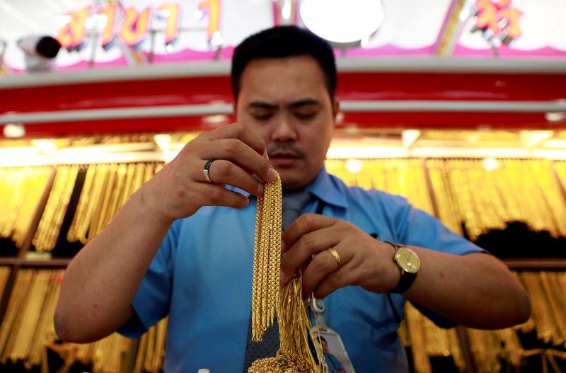 A man holds necklaces in a gold shop in Chinatown in Bangkok