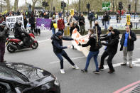 A man tries to rip a banner held by demonstrators blocking traffic during a 'Kill the Bill' protest in London, Saturday, April 3, 2021. The banner read Protect The Right To Protest. The demonstration is against the contentious Police, Crime, Sentencing and Courts Bill, which is currently going through Parliament and would give police stronger powers to restrict protests. (AP Photo/Alberto Pezzali)