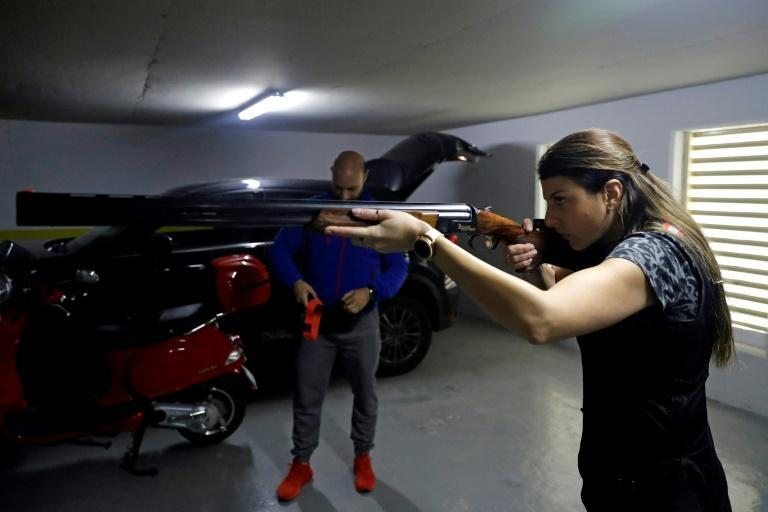 With Lebanon's shooting clubs closed by a strict lockdown, Olympic trap shooter Ray Bassil trains with a virtual shotgun on a makeshift range in the car park of her apartment block