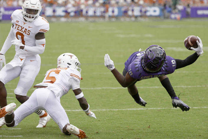 TCU wide receiver JD Spielman (10) dives backwards over the goal line to score a touchdown as Texas defensive back D'Shawn Jamison (5) and teammate and linebacker DeMarvion Overshown (0) look on during the first half of an NCAA college football game Saturday, Oct. 2, 2021, in Fort Worth, Texas. (AP Photo/Ron Jenkins)