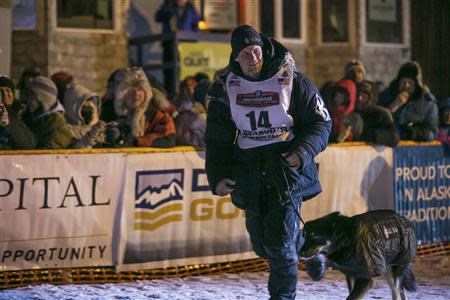 Dallas Seavey runs with his lead dog after winning the Iditarod dog sled race in Nome