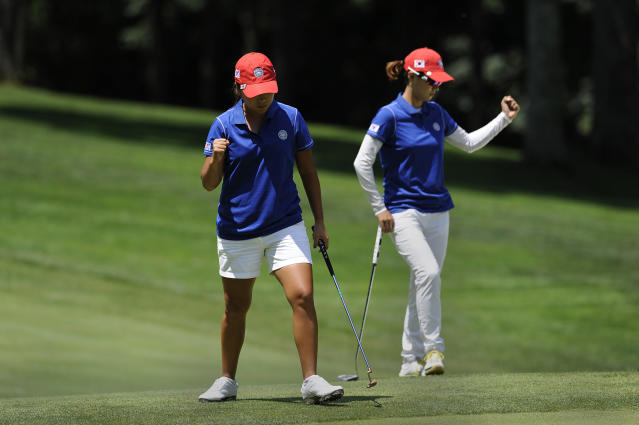 I.K. Kim, left, and Na Yeon Choi, of South Korea, celebrate a birdie on the first hole during the third round of the International Crown golf tournament on Saturday, July 26, 2014, in Owings Mills, Md.(AP Photo/Gail Burton)