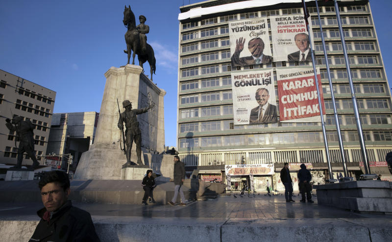 An unemployed man stands next to a statue depicting Turkey's War of Independence in old part of Turkish capital, Ankara, Turkey, Friday, March 29, 2019. A poster with images of Turkey's President Recep Tayyip Erdogan, top left, Devlet Bahceli, leader of the opposition Nationalist Movement Party, MHP, top right, and Mehmet Ozhaseki, the mayoral candidate for Ankara of Erdogan's ruling Justice and Development Party, AKP, and MHP is in the background, ahead of local elections scheduled for March 31, 2019. (AP Photo/Burhan Ozbilici)