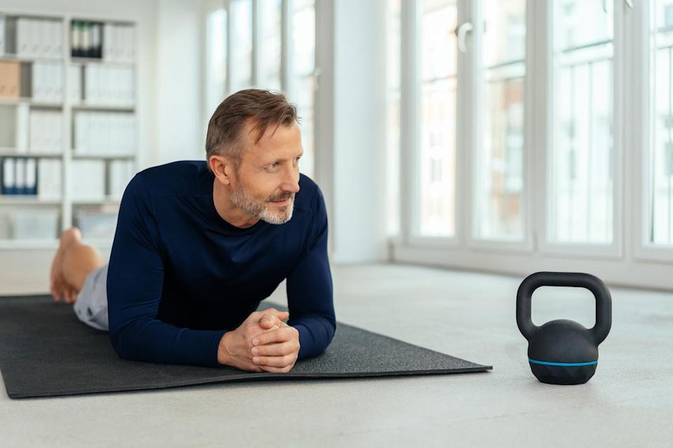 Man resting on a gym mat alongside a kettle weight as he takes a break from working out in a health and fitness concept