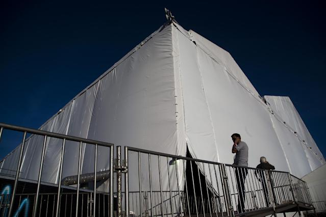 A journalist speaks outside the large tent where the 2014 soccer World Cup draw will take place in Costa do Sauipe, Brazil, Wednesday, Dec. 4, 2013. World Cup organizers say they have spent $11 million to organize the 90-minute show that will be beamed around the world on Friday. The mammoth white tent that has been erected on the sand is bigger than most of the world's cathedrals. (AP Photo/Victor R. Caivano)