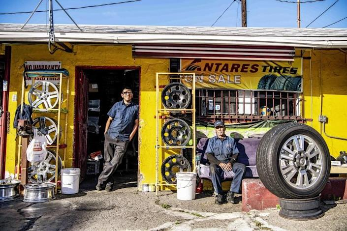 """LOS ANGELES, CA - MARCH 26: Luis Moreno, left, and Author Bernal, both employees at Flaco's Tires on Thursday, March 26, 2020 in Los Angeles, CA. Moreno, who lives with his girlfriend and their 5 year old son, agreed to a pay reduction as business has been hit hard by the coronavirus pandemic. """"We normally do at least fifteen cars a day"""" said Moreno, """"Now, it's maybe four"""". (Mariah Tauger / Los Angeles Times)"""