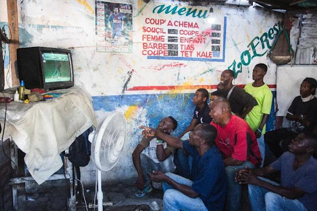 Haitians watch Saturday's World Cup Group Stage match between Argentina and Iceland in a small barber shop in downtown Port-au-Prince (AFP Photo/Pierre Michel Jean)
