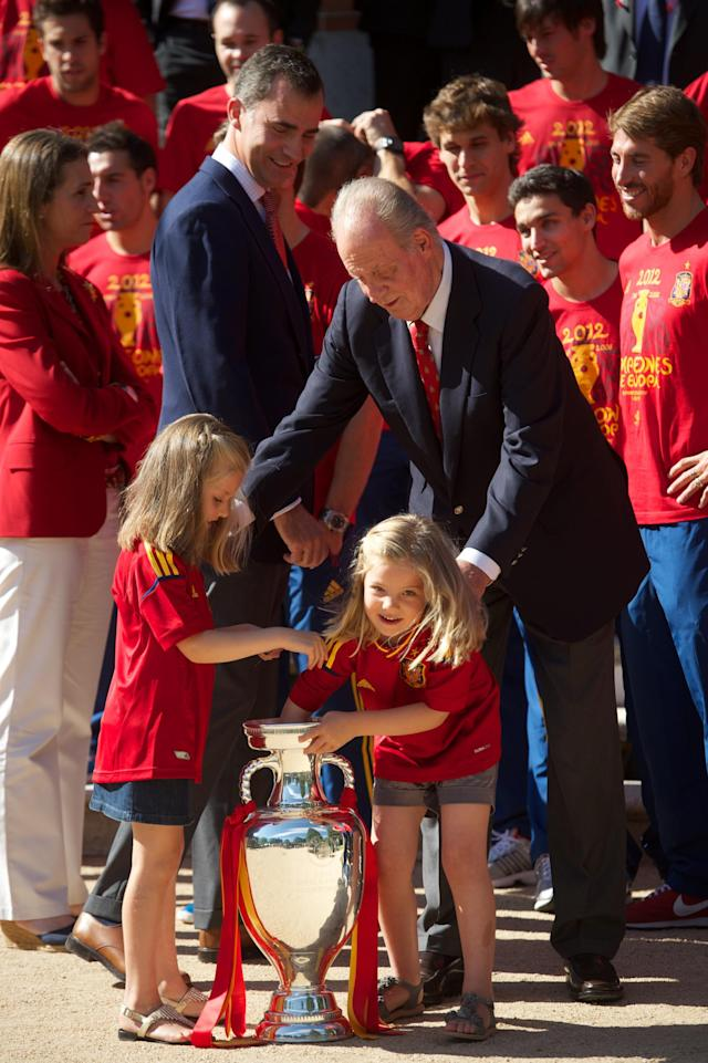 MADRID, SPAIN - JULY 02: (L-R) Prince Felipe of Spain smiles as Princess Leonor of Spain and Princess Sofia of Spain play with the UEFA EURO 2012 trophy next to King Juan Carlos I of Spain as they receive the players of the victorious Spain team at Zarzuela Palace on July 2, 2012 in Madrid, Spain. (Photo by Pool/Getty Images)