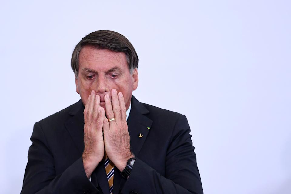 "TOPSHOT - Brazilian President Jair Bolsonaro gestures during the launch of a program for the resumption of tourism, a sector severely affected by the new coronavirus outbreak, at Planalto Palace in Brasilia, on November 10, 2020. - Brazil's decision to halt trials of a Chinese-developed Covid-19 vaccine triggered a politically charged row Tuesday as a top health official expressed ""indignation"" and far-right President Jair Bolsonaro claimed the ruling as a personal victory. (Photo by EVARISTO SA / AFP) (Photo by EVARISTO SA/AFP via Getty Images)"