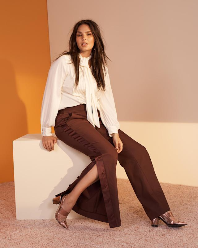 Candice Huffine wears a tie-neck blouse and dark brown split-leg trousers from the new Prabal Gurung x Lane Bryant collection. (Photo: Courtesy of Lane Bryant)
