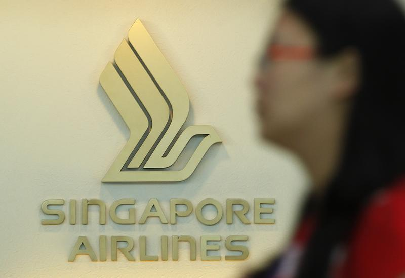 A woman walks past a SIA logo at a ticketing booth at Changi airport in Singapore