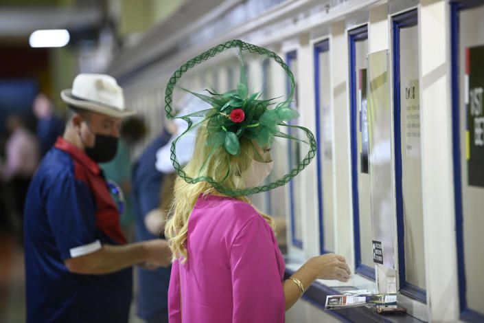 A woman wears a hat while placing a bet during the Preakness Stakes horse race at Pimlico Race Course, Saturday, May 15, 2021, in Baltimore. (AP Photo/Nick Wass)
