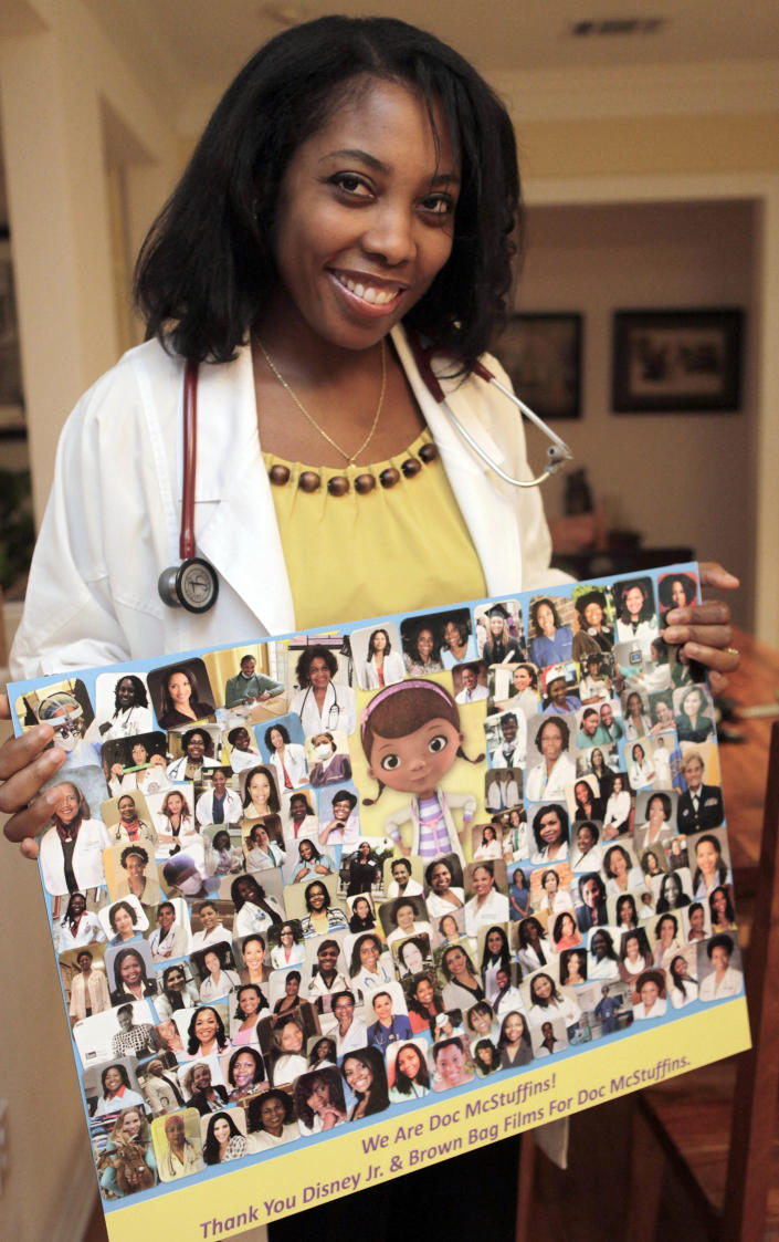 """This June 7, 2012 photo shows Dr. Myiesha Taylor holding a collage of fellow doctors supporting Disney Junior's animated series """"Doc McStuffins"""" at her home in Keller, Texas. For black women whose own wish to practice medicine come true, the show is welcome affirmation. The doctors shown in the collage are graduates of schools including Harvard, Yale and Stanford and work in a range of specialities such as neurosurgery, orthopedic surgery and psychiatry. Taylor is a board-certified emergency room physician. (AP Photo/LM Otero)"""