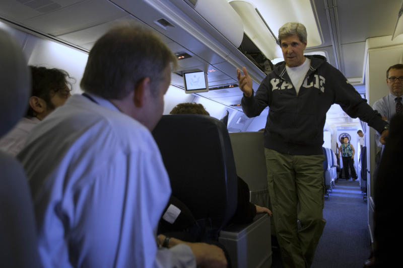 U.S. Secretary of State John Kerry speaks to the traveling press on board the airplane as he leaves Doha, Qatar en route to New Delhi, on Sunday, June 23, 2013. In Qatar Kerry spent time discussing Syria and Afghanistan. (AP Photo/Jacquelyn Martin, Pool)