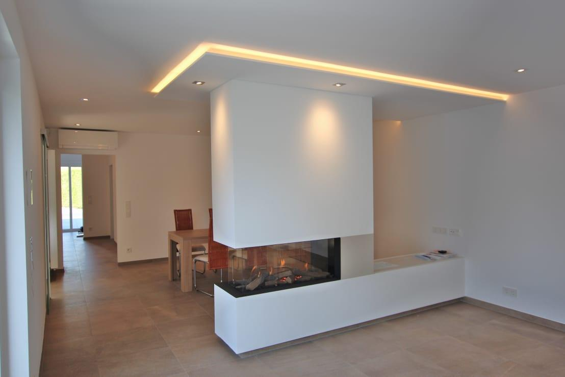 <p>How unusual is this? Instead of perimeter ceiling lighting that would run around the entire edge of the ceiling, just a small section has been given the inset treatment, in a bid to make more of a feature of the chic fireplace. Imagine the cosiness of this room when all other lighting is switched off and only the feature installation and flickering flames light the space!</p>  Credits: homify / Queck—Elektroanlagen