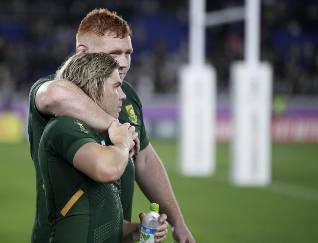 South Africa's Faf de Klerk is embraced by teammate Steven Kitshoff following their Rugby World Cup Pool B game at International Stadium between New Zealand and South Africa in Yokohama, Japan, Saturday, Sept. 21, 2019. New Zealand defeated South Africa 23-13. (AP Photo/Jae Hong)