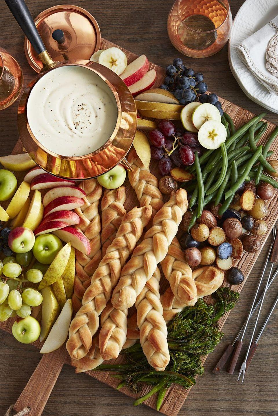 """<p>It doesn't get much easier than these braided breadsticks. You can use either store-bought or homemade pizza dough in this recipe—but your guests won't know the difference. They'll be too busy enjoying the decadent <a href=""""https://www.countryliving.com/food-drinks/a28068814/three-cheese-fondue-recipe/"""" rel=""""nofollow noopener"""" target=""""_blank"""" data-ylk=""""slk:three-cheese fondue"""" class=""""link rapid-noclick-resp"""">three-cheese fondue</a>. </p><p><strong><a href=""""https://www.countryliving.com/food-drinks/a28069249/cable-knit-breadsticks-recipe/"""" rel=""""nofollow noopener"""" target=""""_blank"""" data-ylk=""""slk:Get the recipe"""" class=""""link rapid-noclick-resp"""">Get the recipe</a>.</strong></p><p><strong><a class=""""link rapid-noclick-resp"""" href=""""https://www.amazon.com/Nordic-Ware-Natural-Aluminum-Commercial/dp/B0049C2S32?tag=syn-yahoo-20&ascsubtag=%5Bartid%7C10050.g.1078%5Bsrc%7Cyahoo-us"""" rel=""""nofollow noopener"""" target=""""_blank"""" data-ylk=""""slk:SHOP BAKING SHEETS"""">SHOP BAKING SHEETS</a><br></strong></p>"""