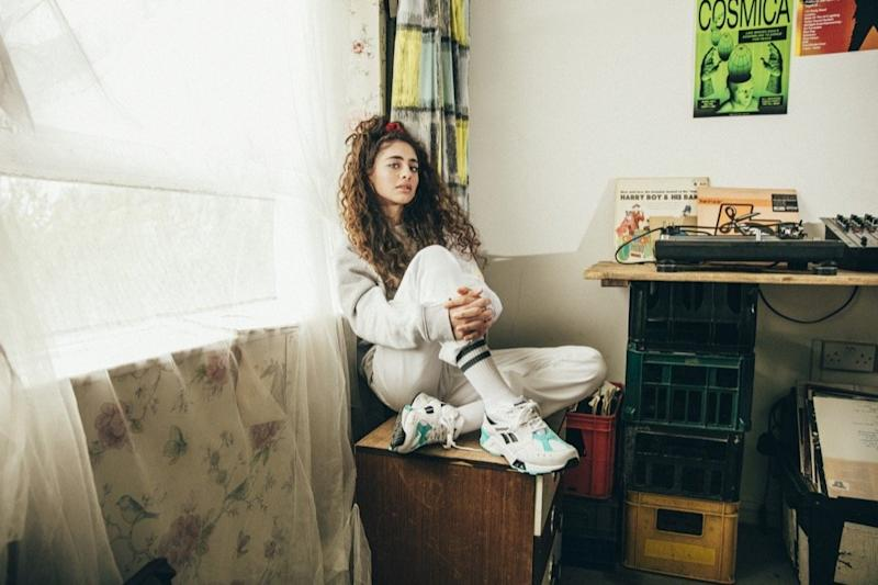 Woman sitting on a dresser and wearing Reebok apparel and sneakers