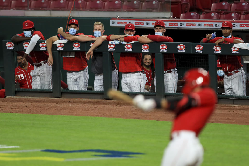 Members of the Cincinnati Reds wear masks as they watch the game from the dugout during an exhibition baseball game against the Detroit Tigers at Great American Ballpark in Cincinnati, Tuesday, July 21, 2020. The Reds won 9-7. (AP Photo/Aaron Doster)