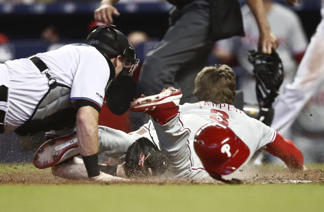 Miami Marlins catcher Chad Wallach, left, tags out Philadelphia Phillies' Bryce Harper (3) at home plate during the sixth inning of a baseball game Sunday, April 14, 2019, in Miami. (AP Photo/Brynn Anderson)