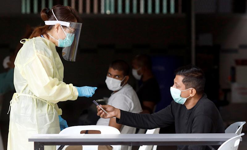 A medical professional talks to migrant workers as they wait to be transported to a medical facility from their dormitory, amid the coronavirus disease (COVID-19) outbreak, in Singapore April 27, 2020. REUTERS/Edgar Su