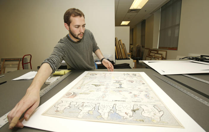 """In this Wednesday, Oct. 23, 2013 photo, Jeremy Stone frames a Billy Ireland comic strip from Dec. 11, 1921 called """"The Passing Show"""" at the Billy Ireland Cartoon Library & Museum in Columbus, Ohio. Today the museum collection includes more than 300,000 original strips from everybody who's anybody in the newspaper comics world, plus 45,000 books, 29,000 comic books and 2,400 boxes of manuscript material, correspondence and other personal papers from artists. (AP Photo/Tony Dejak)"""