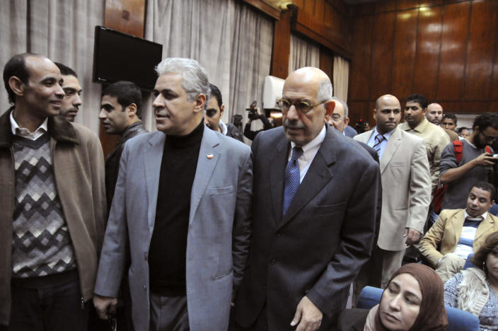 """Egyptian opposition leaders Hamdeen Sabahi, second left, and Mohamed ElBaradei, center, arrive for a press conference in Cairo, Egypt, Wednesday, Dec. 5, 2012. Supporters and opponents of Egyptian leader Mohammed Morsi pelted each other with rocks and firebombs and fought with sticks outside the presidential palace in Cairo on Wednesday, as a new round of protests deepened the country's political crisis. Mohamed ElBaradei, a leading opposition advocate of reform and democracy, accused the president's supporters of a """"vicious and deliberate"""" attack against peaceful demonstrators.(AP Photo/Ahmed Hammad)"""