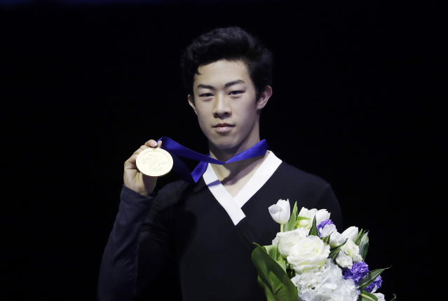 United States' Nathan Chen celebrates on the podium after winning a men's competition at the Figure Skating World Championships in Assago, near Milan, Saturday, March 24, 2018. (AP Photo/Luca Bruno)