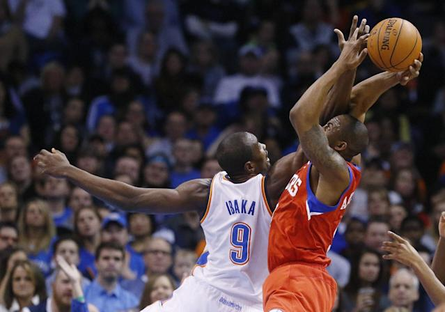 Philadelphia 76ers guard James Anderson (9) is fouled by Oklahoma City Thunder forward Serge Ibaka (9) during the second quarter of an NBA basketball game in Oklahoma City, Tuesday, March 4, 2014. (AP Photo/Sue Ogrocki)